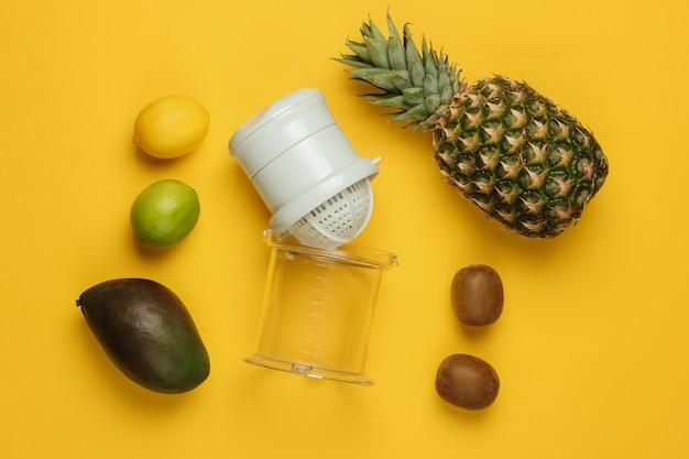 Spremiagrumi manuale in plastica e frutti tropicali su sfondo giallo. concetto di cibo sano. succhi di frutta appena spremuti. vista dall'alto