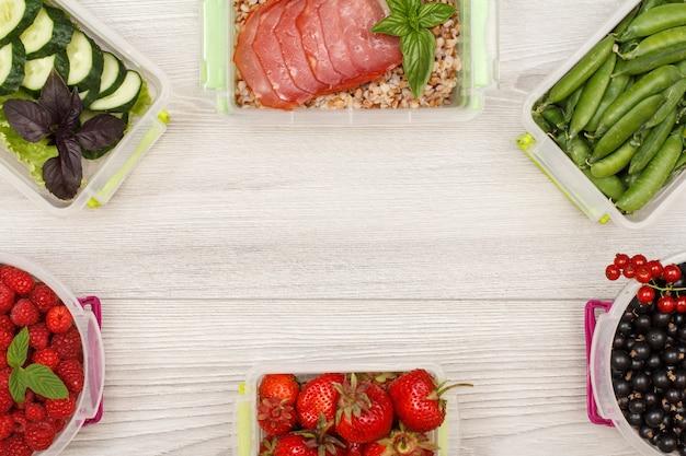 Contenitori per alimenti in plastica con ribes, fragole, lamponi, piselli, porridge di grano saraceno.