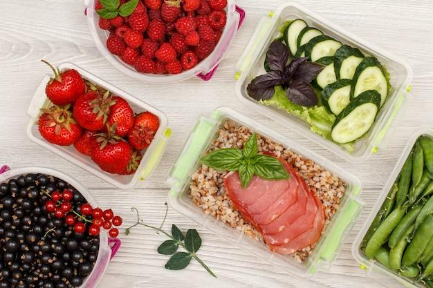 Contenitori di plastica per la preparazione dei pasti con porridge di grano saraceno bollito e fette di carne, cetrioli freschi.