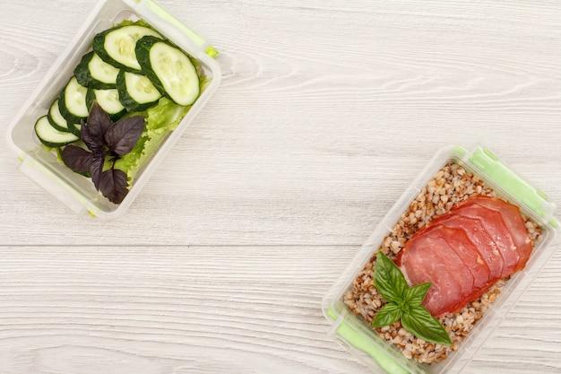 Contenitori di plastica per la preparazione dei pasti con porridge di grano saraceno bollito, fette di carne e cetrioli freschi.
