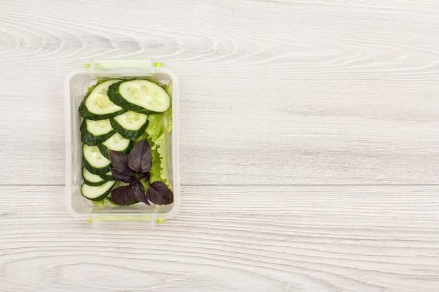 Contenitori di plastica per la preparazione dei pasti con cetrioli freschi e insalata su sfondo grigio.