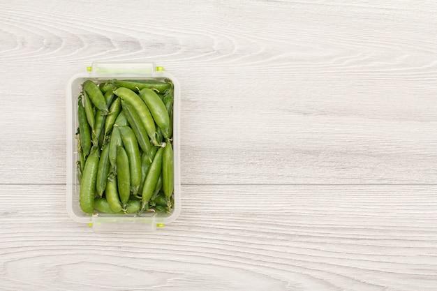 Contenitori di plastica per la preparazione dei pasti con piselli freschi su sfondo grigio. vista dall'alto con copia spazio.