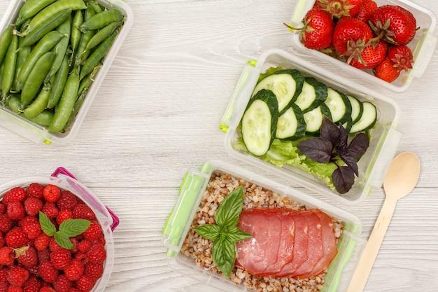 Contenitori di plastica per la preparazione dei pasti con fragole fresche, lamponi, porridge di grano saraceno bollito.