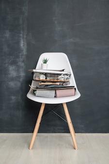 Sedia da ufficio in plastica con pila di articoli di cancelleria, documenti, campioni di tessuto piegato e piccolo vaso di fiori con pianta verde