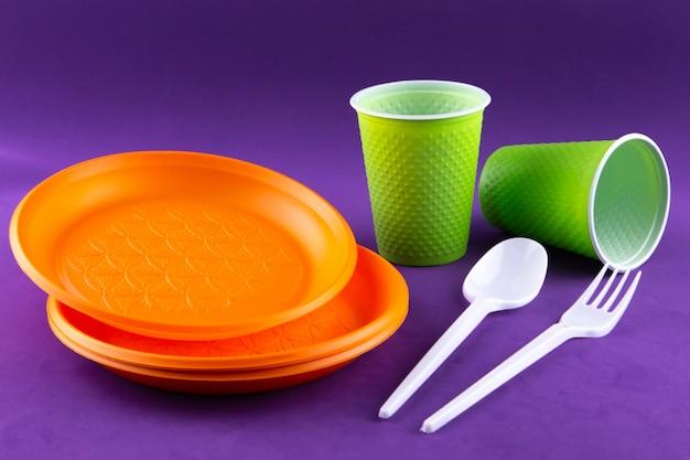 Raccolta di rifiuti di plastica verde arancio sulla porpora
