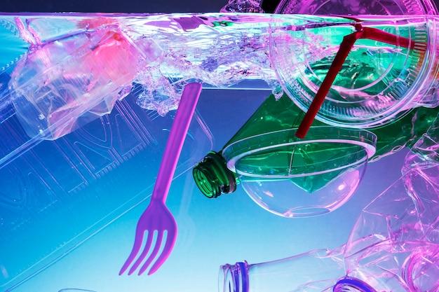 Plastica e altri rifiuti che inquinano lo sfondo al neon dell'oceano