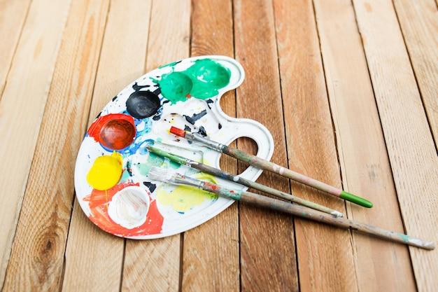 Tavolozza di vernice di plastica con vernice e pennelli sul tavolo di legno
