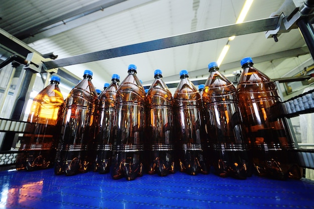 Bottiglie in plastica pet in plastica gialla con coperchi blu con birra o bevande dolci su un nastro trasportatore sullo sfondo della fabbrica. produzione alimentare industriale di bevande.