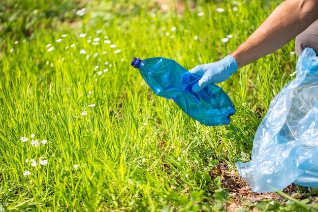 Pianeta di plastica, uomo che raccoglie bottiglia di plastica, raccolta dei rifiuti in una foresta, aiuta l'ambiente di beneficenza della raccolta dei rifiuti, raccolta dei rifiuti