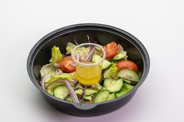 Zolla di plastica con insalata di verdure su una priorità bassa bianca isolata. avvicinamento. consegna di una corretta alimentazione