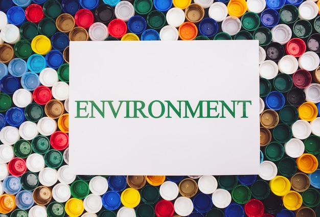 Concetto di inquinamento di plastica. sii privo di plastica. carta con l'ambiente di parola su sfondo colorato di coperchi di plastica diversi, vista dall'alto. materie plastiche monouso, direttiva europea ue per aiutare l'ambiente