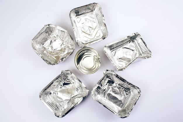 Concetto di inquinamento di plastica. lattina di metallo al centro dei contenitori di alluminio per alimenti sulla superficie bianca, vista dall'alto. plastica monouso. nuove regole per ridurre i rifiuti di plastica, direttiva ue.