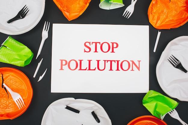 Concetto di inquinamento di plastica. carta con parole fermare l'inquinamento al centro di piatti di plastica rotti colorati usa e getta e forchette su sfondo scuro. concetto di giornata mondiale della terra - senza plastica.