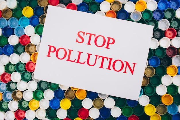Concetto di inquinamento di plastica. rifiuta il concetto di plastica monouso. carta con parole fermare l'inquinamento sulla superficie colorata di diversi coperchi in plastica, vista dall'alto.