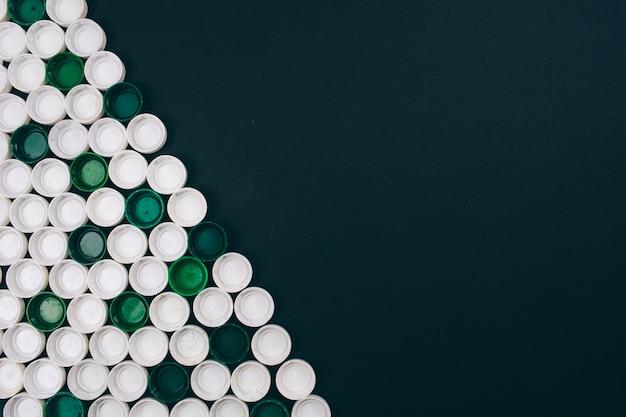 Concetto di inquinamento di plastica. coperchi di plastica bianchi e verdi su fondo scuro situati in diagonale. plastica monouso. rifiuta il concetto di plastica monouso. salva l'ecologia