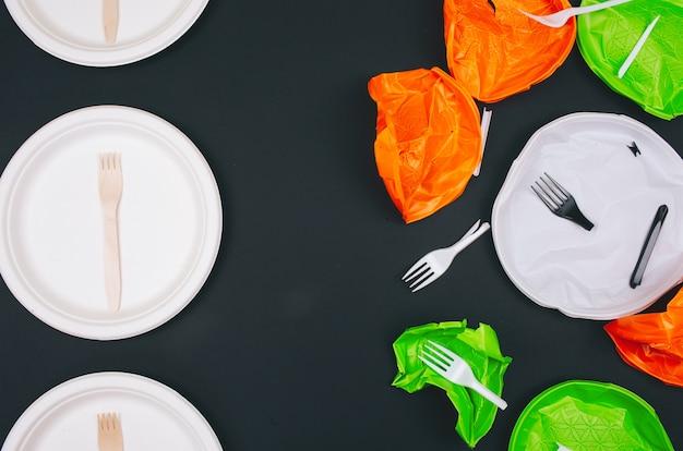 Concetto di inquinamento di plastica. piatti e forchette di plastica ininterrotti e monouso in legno su oscurità.