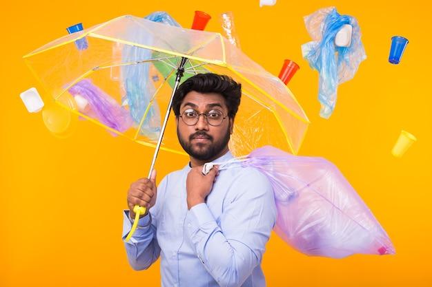 Problema di riciclaggio della plastica, ecologia e concetto di disastro ambientale - uomo indiano che si nasconde dalla spazzatura sotto un ombrello sul muro giallo