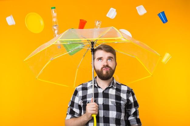 Problema di riciclaggio della plastica, inquinamento e concetto di disastro ambientale - uomo indiano serio che pensa all'ecologia sotto un ombrello su sfondo giallo.