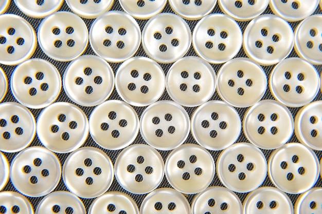 Bottoni lucidi in plastica per vestiti su uno sfondo di tessuto. moda e abbigliamento. industria di fabbrica