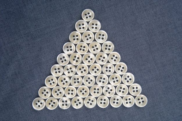 Bottoni in plastica lucidi per vestiti su uno sfondo di tessuto.