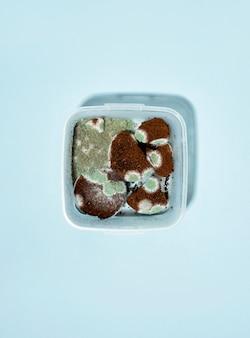 Contenitore quadrato in plastica con muffa e sporcizia nel caffè su sfondo blu. tendenza ombra dura. orizzontale