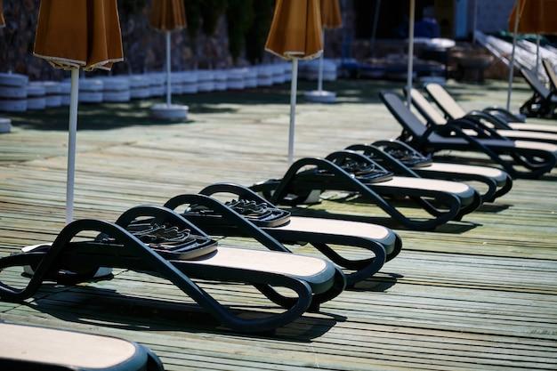 Lettini di plastica in fila sul molo sulla spiaggia in riva al mare