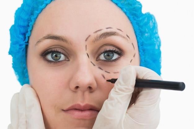 Chirurgo plastico che disegna intorno all'occhio
