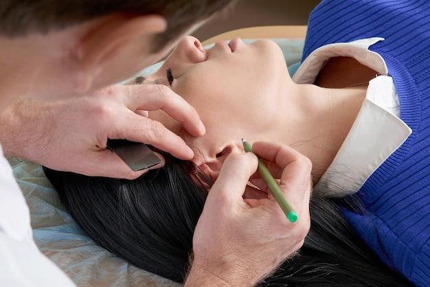 Il chirurgo plastico esamina l'orecchio del paziente prima della chirurgia plastica