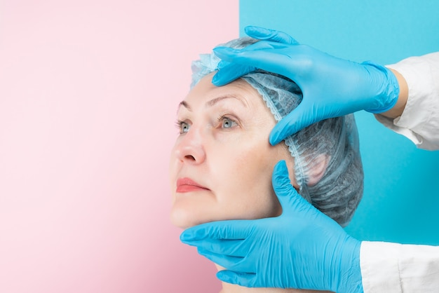 Il chirurgo plastico in guanti medicali sta esaminando il viso di una bella donna di mezza età, il concetto di chirurgia plastica
