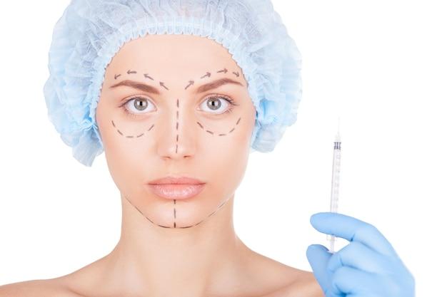 Chirurgia plastica. bella giovane donna in copricapo medico e schizzi sul viso guardando la telecamera mentre qualcuno tiene una siringa vicino al suo viso isolato su bianco