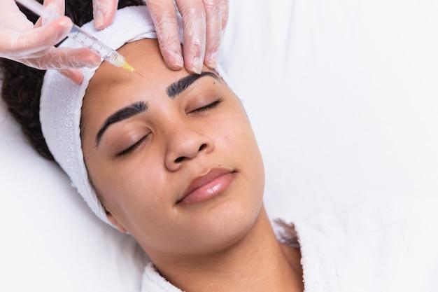 Chirurgia plastica. giovane donna africana che riceve l'iniezione di botox nella zona di interbrow alla clinica di bellezza, primo piano, spazio della copia. giovane donna africana che ottiene l'iniezione di botox nella sua fronte.