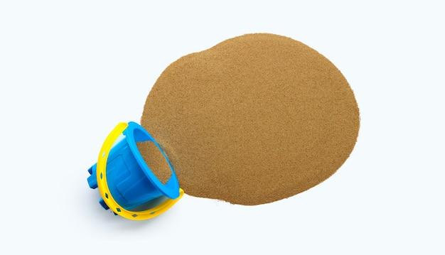 Giocattolo di plastica, secchio blu con sabbia su superficie bianca.