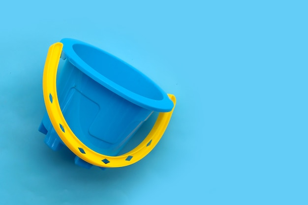Giocattolo di plastica, secchio sulla superficie blu.