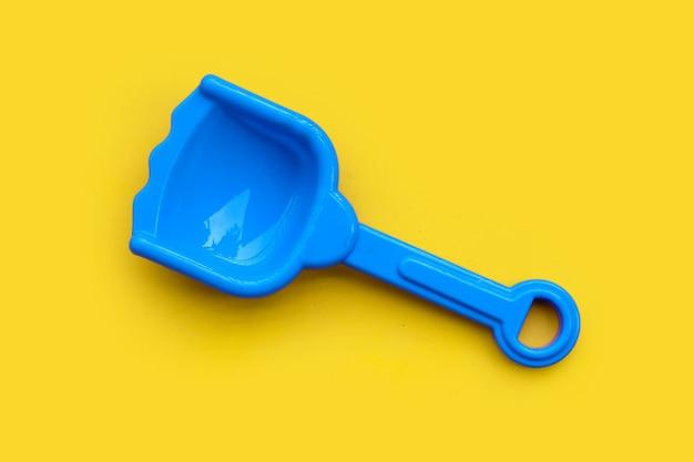Giocattolo di plastica, pala su superficie gialla.