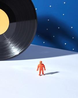 Giocattolo di plastica di astronauta con stelle e disco in vinile nero come un pianeta