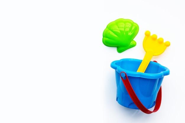 Giocattoli di plastica, pala in secchio per sabbia su superficie bianca. Foto Premium