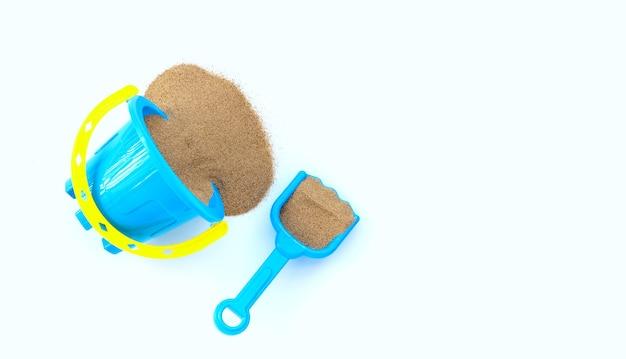 Giocattoli di plastica, pala e secchio con sabbia su superficie bianca