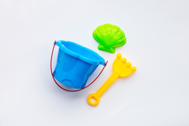 Giocattoli di plastica, pala con secchio per sabbia su superficie bianca.
