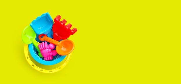 Giocattoli di plastica, pale nel secchio per sabbia sulla superficie verde