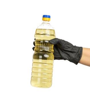 Bottiglia di plastica trasparente con olio di girasole in mano, da vicino