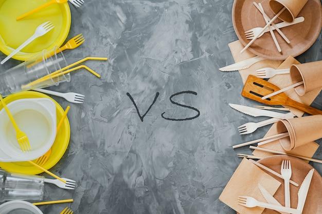 Concetto di scelta di stoviglie in plastica vs sostenibile. in alto, vedi foto di plastica bianca e gialla e utensili in legno confrontati su sfondo grigio.