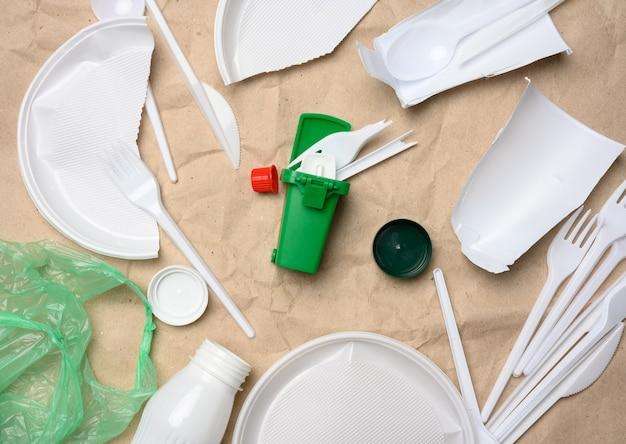 Rifiuti di plastica su carta kraft marrone, inquinamento ambientale, vista dall'alto