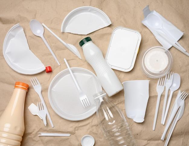 Rifiuti di plastica dalla vita sullo sfondo della carta kraft marrone, inquinamento ambientale, vista dall'alto Foto Premium