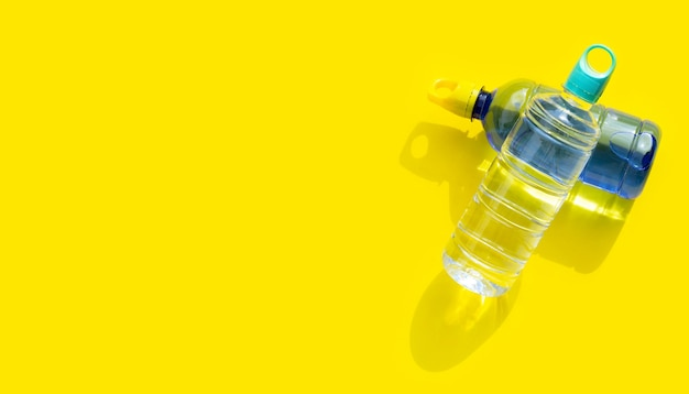 Bottiglie d'acqua in plastica sulla superficie gialla