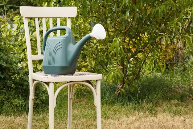 Annaffiatoio di plastica sulla vecchia sedia in uno sfondo naturale. attrezzi da giardino.