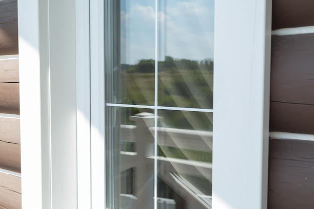 Barre di plastica bianche per finestre con il riflesso del cielo nuvoloso blu con alberi verdi