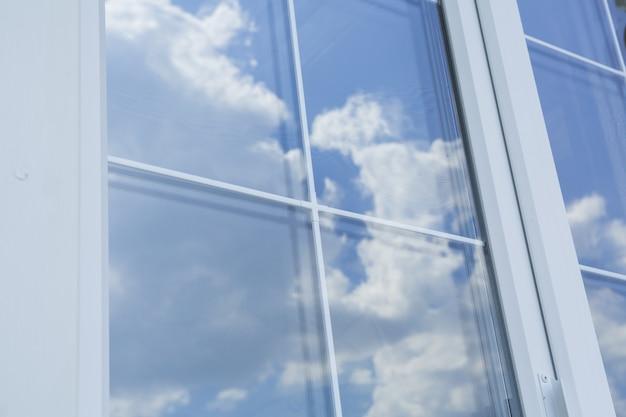 Barre di plastica bianche per finestre con il riflesso del cielo nuvoloso blu