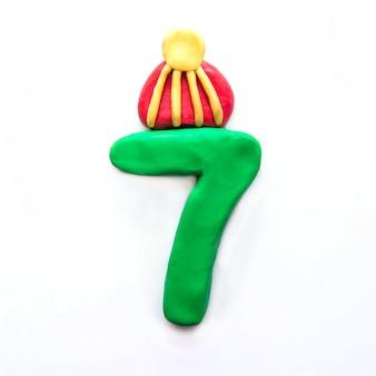 Plastilina verde numero 7 sette nel cappello invernale su sfondo bianco