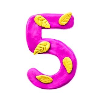 Numero 5 di plastilina rosa con foglie autunnali gialle, isolato su sfondo bianco