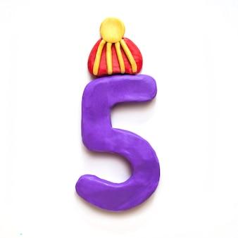 Plastilina viola numero 5 cinque nel cappello invernale con pompon su sfondo bianco